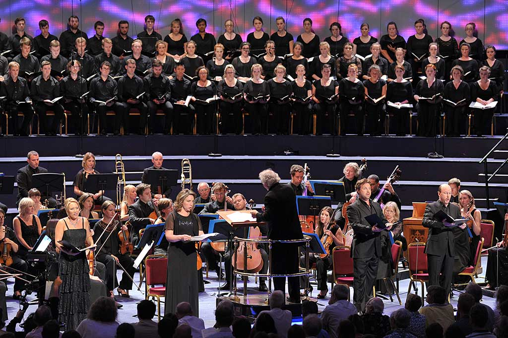 (L – R) Carolyn Sampson (soprano), Christine Rice (mezzo-soprano), conductor Donald Runnicles, Jeremy Ovenden (tenor), Neal Davies (bass), the National Youth Choir of Scotland and the BBC Scottish Symphony Orchestra perform the Mozart Requiem for the BBC Proms 2014. Photograph: BBC/Chris Christodoulou