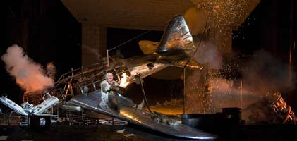 Mime sits on the crashed plane (Act 1: Siegfried) from which the Wanderer appears. ©Clive Barda