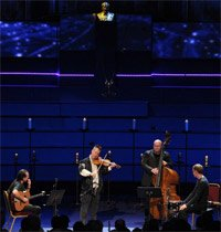 Nigel Kennedy performing 'Das Pendel' at the BBC Proms on 6 August 2011 with Rolf Bussald (guitar), Yaron Stavi (double bass) and Krzysztof Dziedzic (percussion). Photograph: BBC/Chris Christodoulou